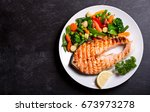 plate of grilled salmon steak... | Shutterstock . vector #673973278