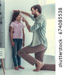 handsome young dad is measuring ... | Shutterstock . vector #674085538