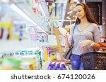 young woman buying milk in... | Shutterstock . vector #674120026
