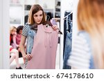 Stock photo young woman choosing new pink dress in a fashion boutique 674178610