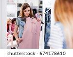 young woman choosing new pink... | Shutterstock . vector #674178610
