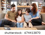 family sitting on sofa in... | Shutterstock . vector #674413870
