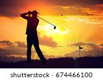 Silhouette of man playing golf...