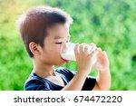 young asian thai boy drinking... | Shutterstock . vector #674472220