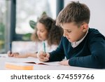 concentrated schoolboy sitting... | Shutterstock . vector #674559766