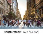 Small photo of NEW YORK CITY - CIRCA 2017: Busy crowds of people cross the intersection of 5th Avenue and 23rd Street in Manhattan, New York City with the colorful setting sun in the background on June 3rd, 2017.