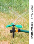 Close up of lawn sprinkler in hot summer day - stock photo