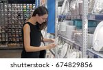 young woman chooses plates in... | Shutterstock . vector #674829856