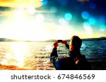 Film grain effect.  Tall ginger hair man tourist taking photos or video with mobile phone. Autumn sunny day at sea coastline  - stock photo