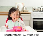 baby girl eating at home | Shutterstock . vector #674906440