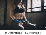 Small photo of Pretty and confident sportive girl sitting on the bench in gym and morally preparing for fighting. She has put her hands on th lap. Close up