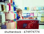 sad boy in a shopping cart.... | Shutterstock . vector #674974774