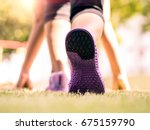 Small photo of Ready steady go. Closeup of running shoes on grass, young lady on start position and going to run in park.