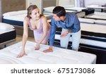 happy couple choosing... | Shutterstock . vector #675173086