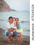 Small photo of Friendly family having fun on a beach. Father and daughters. Zakynthos, Greece. Ionic Sea