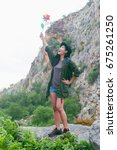 Small photo of Hiking in the mountains in little Asian. Woman traveler with a backpack on a hiking trip in the mountains in the summer holidays. The mountain lifestyle, adventure and sports.