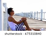 lonely man is sitting by pier | Shutterstock . vector #675310840