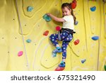 little girl climbing a rock... | Shutterstock . vector #675321490