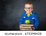 Small photo of Smiling happy clever boy in a glasses and with backpack. Child with a pile of books with green apple in his hands. With a blackboard on a background. Ready for school. Back to school.