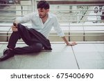 Small photo of Unemployee businessman sitting on walkway