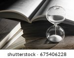 hourglass and open book on... | Shutterstock . vector #675406228