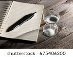 hourglasses and book on a... | Shutterstock . vector #675406300
