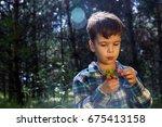 baby boy eating strawberries in ... | Shutterstock . vector #675413158