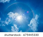Small photo of The phenomenon of the sun halo is showing with the flare behind the blue clear and little cloud sky. It occurred by the refraction of the sunlight with moisture in the innermost atmosphere.