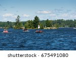 boats on lake muskoka passing... | Shutterstock . vector #675491080