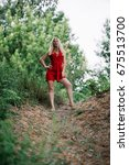 Small photo of Beautiful blonde woman in a red romper looks at the camera dominantly, summer park background