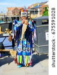 Small photo of Whitby, North Yorkshire, England - July 1, 2017:,UK - Peruvian busker plays pan flute, singing and dancing on street for tourists at Whitby in hot sunny on summer