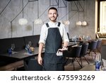 a young  smiling waiter in a... | Shutterstock . vector #675593269