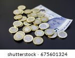 Small photo of New british one sterling pound coins on dark background with a 5 pounds note.