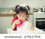 baby girl eating at home | Shutterstock . vector #675617524