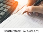 Small photo of Businessman writing on notebook on wooden table, People are recording accounting data calculated from a calculator. To report information to the CEO. Concept finance planing and analyzes management.