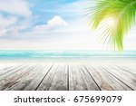 empty wooden table and palm... | Shutterstock . vector #675699079