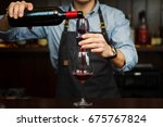 Small photo of Male sommelier pouring red wine through aerator into glass.