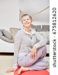 Small photo of Senior citizen making stretching fitness exercise at home
