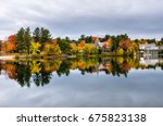 Stock photo buildings among colourful autumnal trees and reflection in water in lake placid ny on a cloudy 675823138