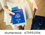 Stock photo closeup of girl holding passports and boarding pass 675951556