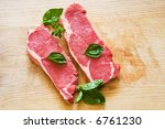 fresh and raw beef steak with green herbs - stock photo