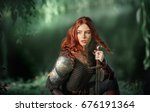 Small photo of Beautiful red haired girl in metal medieval armor dress with swords sitting in warlike pose near river and looking afar. Fairy tale story about warrior . Glowing light. Warm art work.