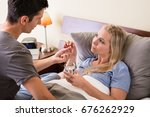 young caring man giving pill... | Shutterstock . vector #676262929