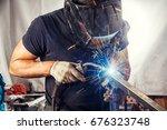 a strong man is a welder in a... | Shutterstock . vector #676323748