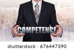 Small photo of A businessman is holding a virtual word. Concept of competence.