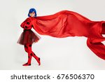 Small photo of Girl with developing a red cape. Woman comic book character. Cosplay girl.