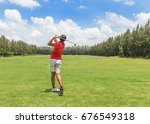 Small photo of golfer in action hit golf shot on golf course yard signs during practice golf driving range with blue sky