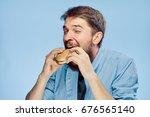 man eating a hamburger on a... | Shutterstock . vector #676565140