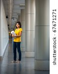 Full length portrait of a smiling college student wearing yellow shirt standing holding books in a modern campus hallway. Female Asian Thai late teens, early 20s of Chinese descent looking at camera - stock photo