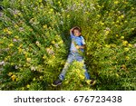 the boy lies in the meadow in... | Shutterstock . vector #676723438